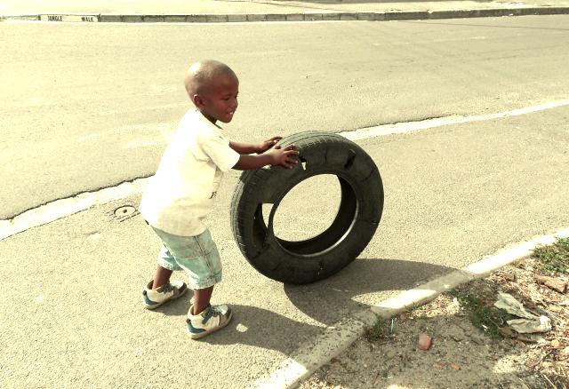 Ein Kind spielt in Langa mit einem Autoreifen.